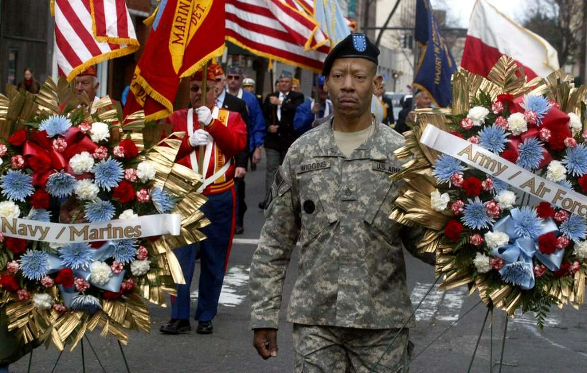 Iraq and Kuwait veteran, Alonzo Wiggins carries a memorial wreath along Main Street during the annual Veterans Day Parade in Bridgeport, Wednesday, Nov. 11, 2009.