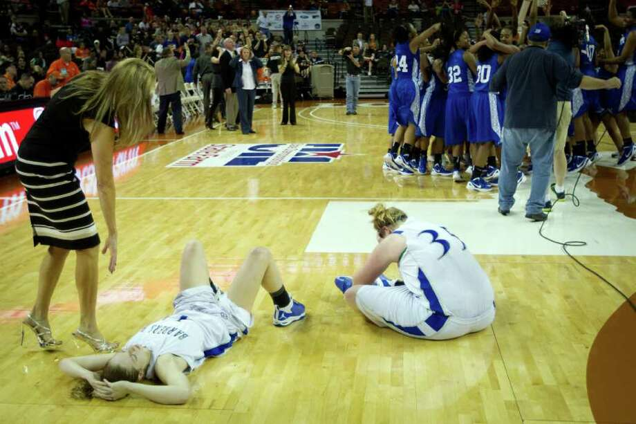 Barbers Hill forward Shannon Evans (11) and center Kendall Shaw (35) collapse on the court as Mansfield Summit players celebrate their victory in a class 4A semifinal game during the UIL girls state basketball tournament at the Frank Erwin Center on Thursday, March 1, 2012, in Austin. Photo: Smiley N. Pool, Houston Chronicle / © 2012  Houston Chronicle