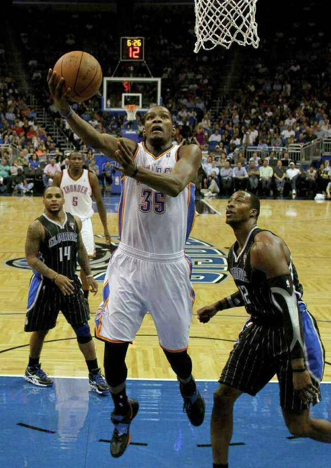 Oklahoma City Thunder's Kevin Durant (35) goes between Orlando Magic's Jameer Nelson (14) and Dwight Howard for a shot during the second half of an NBA basketball game on Thursday, March 1, 2012, in Orlando, Fla. Oklahoma City won 105-102. Photo: AP