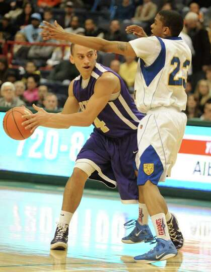 CBA's Chaz Lott passes the ball aroundBishop Maginn's Demere Hannah during a Class AA semifinals bas