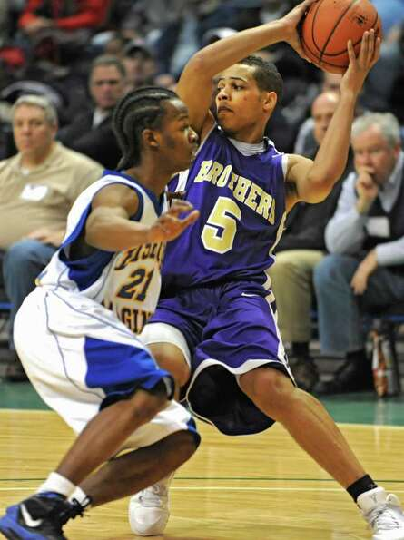 CBA's Christian Leppanen is guarded by Bishop Maginn's Al Bruton during a Class AA semifinals basket