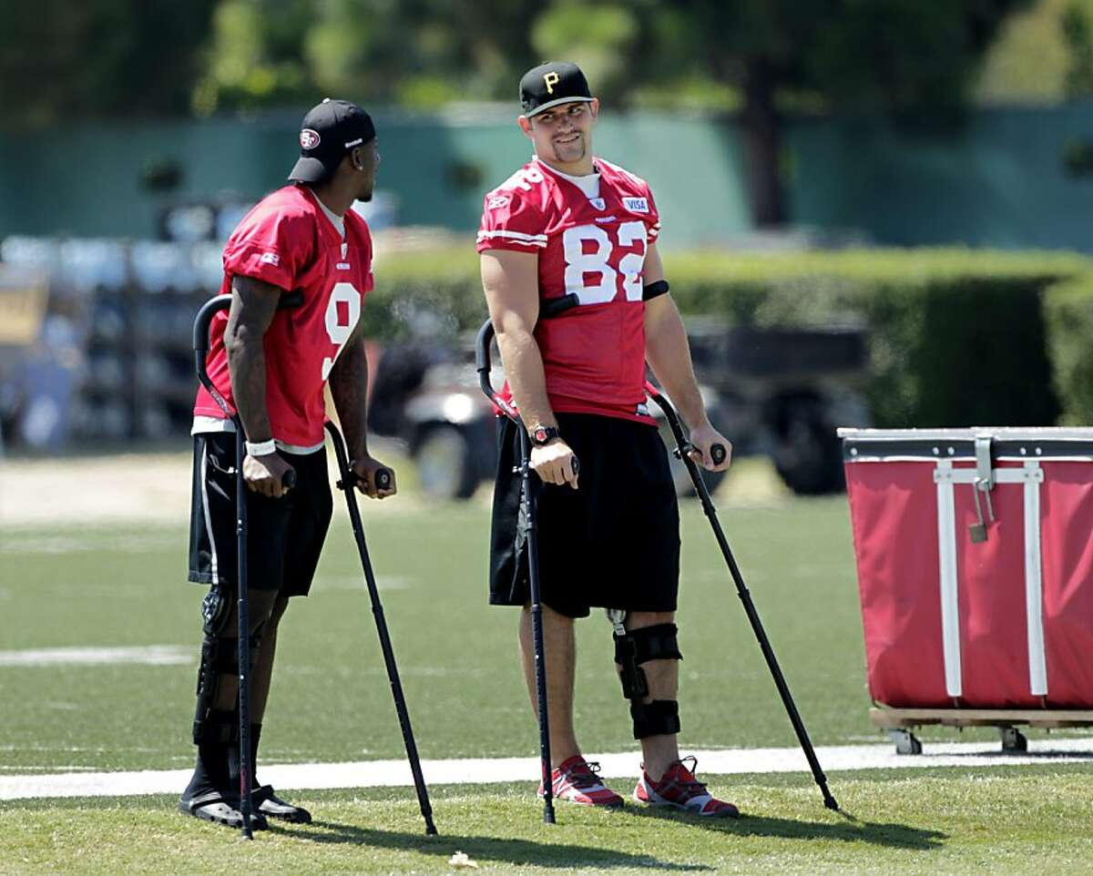 The San Francisco 49ers players Dontavia Bowman, left and Nate Byham both injured talk as they watch their team practice, Tuesday August 2, 2011, in Santa Clara, Calif.