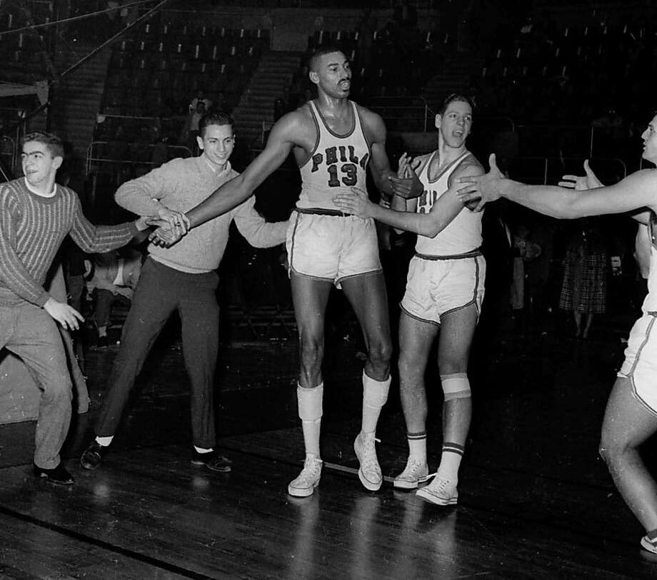 FILE - In this March 2, 1962 file photo, unidentified fans and teammates rush onto court to congratulate Philadelphia Warriors Wilt Chamberlain (13) in Hershey, Pa., after he scored his 100th point in a 169-147 win over the New York Knickerbockers.  For 50 years, Chamberlain's 100-point night has stood as one of sports magic numbers. (AP Photo/Paul Vathis, File) Photo: Paul Vathis, Associated Press
