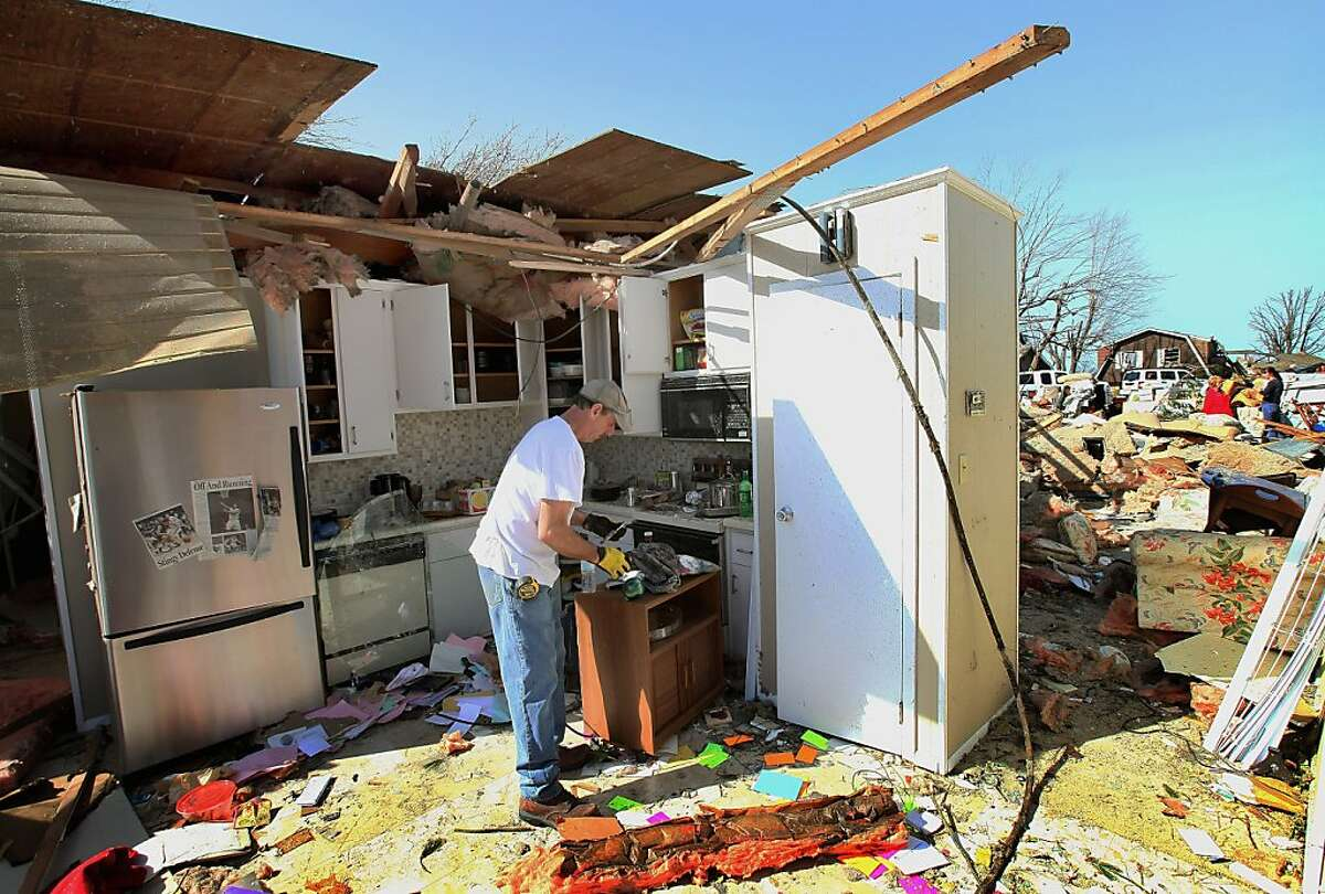 Steve Crabb helps to salvage items at the tornado-damaged home of Linda Branlet on March 1, 2012 in Harrisburg, Illinois. According to reports, at least 13 people died as severe weather and tornados swept through the middle of the country on Tuesday. Six were killed in Harrisburg.