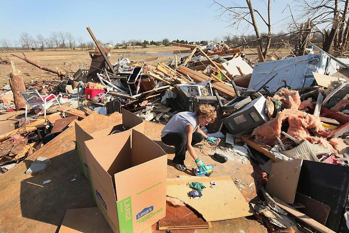 Julie Piche helps to salvage items at the tornado-damaged home of a friend on March 1, 2012 in Harrisburg, Illinois. According to reports, at least 13 people died as severe weather and tornados swept through the middle of the country on Tuesday. Six were killed in Harrisburg.