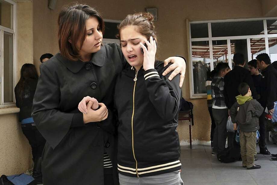 A woman comforts her daughter in a schoolyard  after a fatal shooting of an American gym teacher at a school in Sulaimaniyah, 160 miles (260 kilometers) northeast of Baghdad, Iraq, Thursday, March, 1, 2012. An American gym teacher was killed Thursday when a student in a crowded classroom pulled out a gun, shot the teacher and then shot himself, officials and eyewitnesses said. Photo: Yahya Ahmed, Associated Press