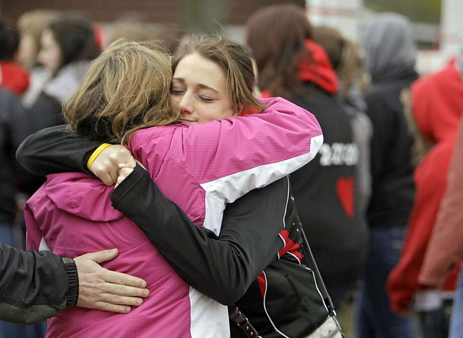 Two students hug on the town square in Chardon, Ohio, Thursday, March 1, before marching to the high school to honor the three students who were killed in a shooting there Monday. The school re-opened to parents and students Thursday and classes resume Friday. Photo: Mark Duncan, Associated Press