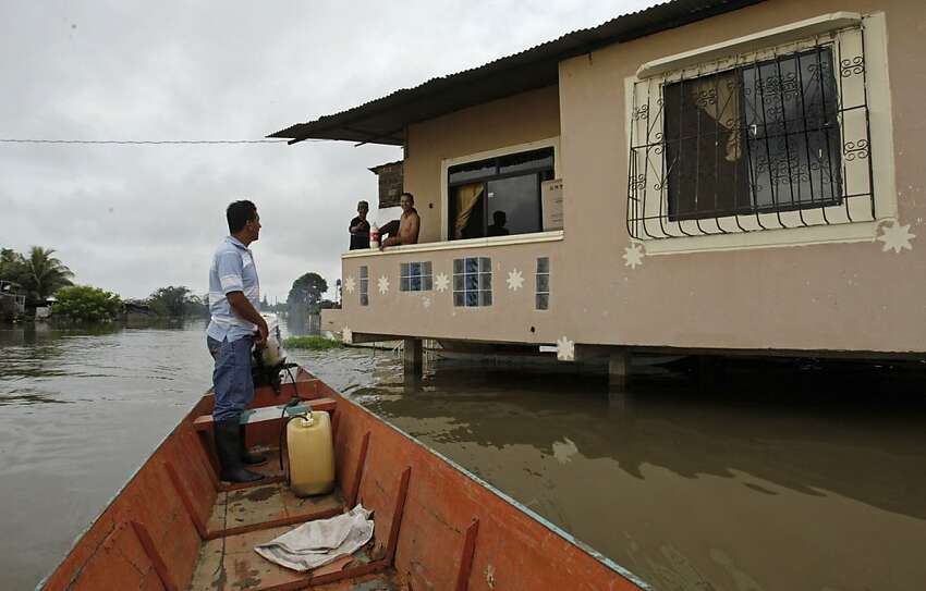 A man chats with his neighbors as he navigates his boat through the flooded streets in Jujan along Ecuador's coast, Thursday March 1, 2012. Heavy rain is causing flooding and landslides and affecting hundreds of people. (AP Photo/Dolores Ochoa)