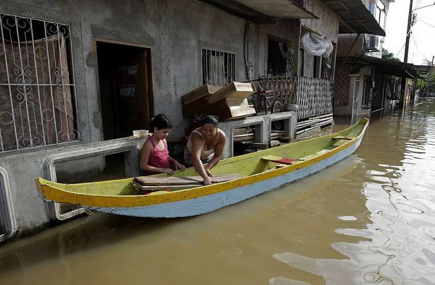 A mother and daughter remove wood planks from their home and place them into a boat in Jujan, Ecuador, Thursday March 1, 2012. Heavy rain is causing flooding and landslides and affecting hundreds of people. (AP Photo/Dolores Ochoa)