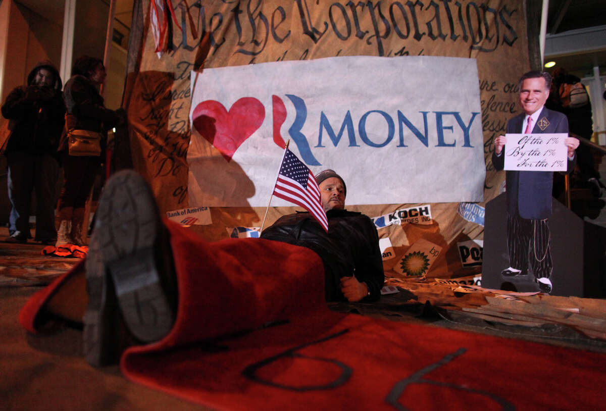 Protester George Karpinski lays under a red carpet laid out by protesters for Mitt Romeny outside of Meydenbauer Center in Bellevue on Thursday, March 1, 2012. The U.S. presidential candidate was hosting an exclusive campaign fundraiser at the convention center in Bellevue.