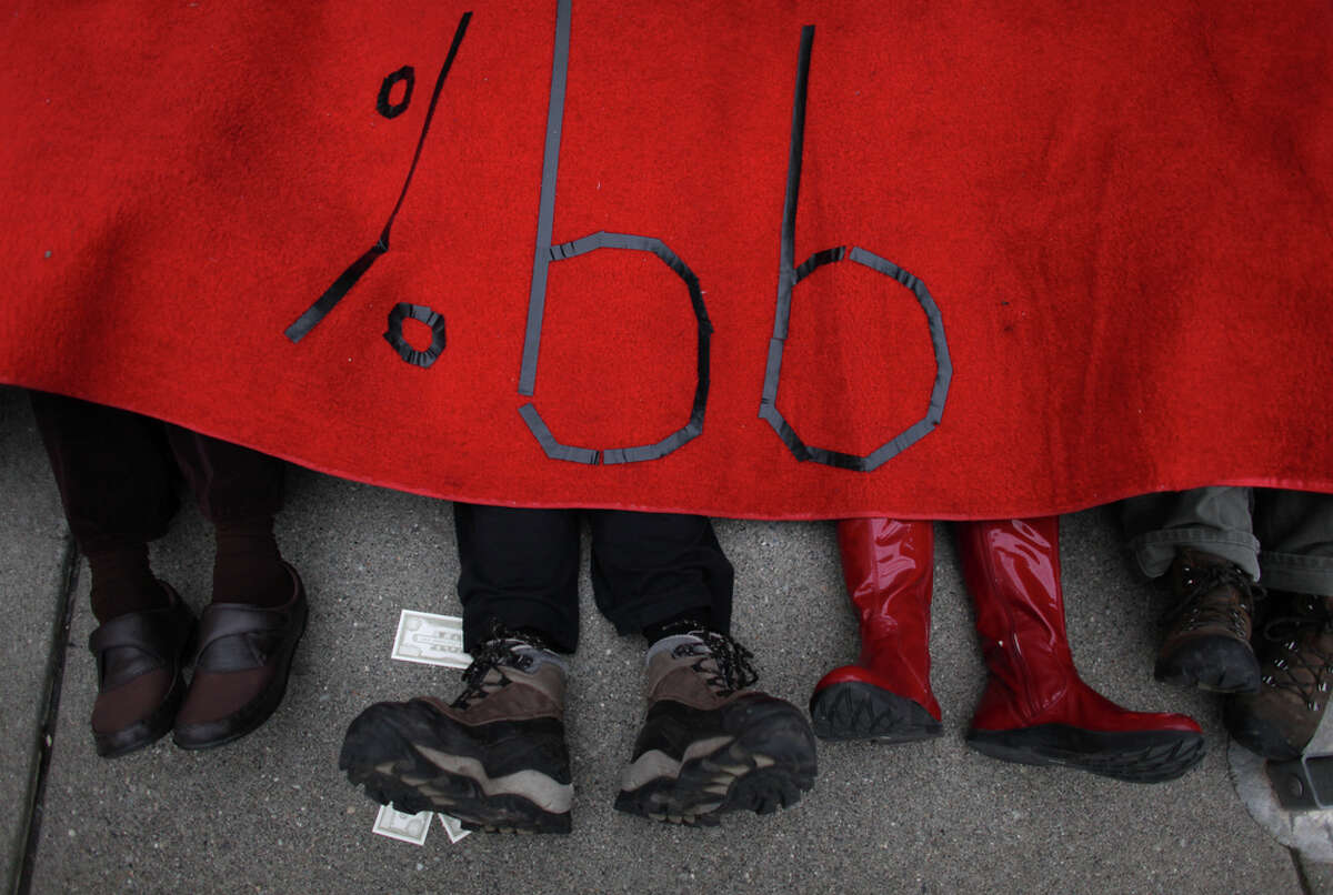 Protesters lie under a red carpet rolled out for Mitt Romeny outside of Meydenbauer Center in Bellevue on Thursday, March 1, 2012. The U.S. presidential candidate was hosting an exclusive campaign fundraiser at the convention center in Bellevue.