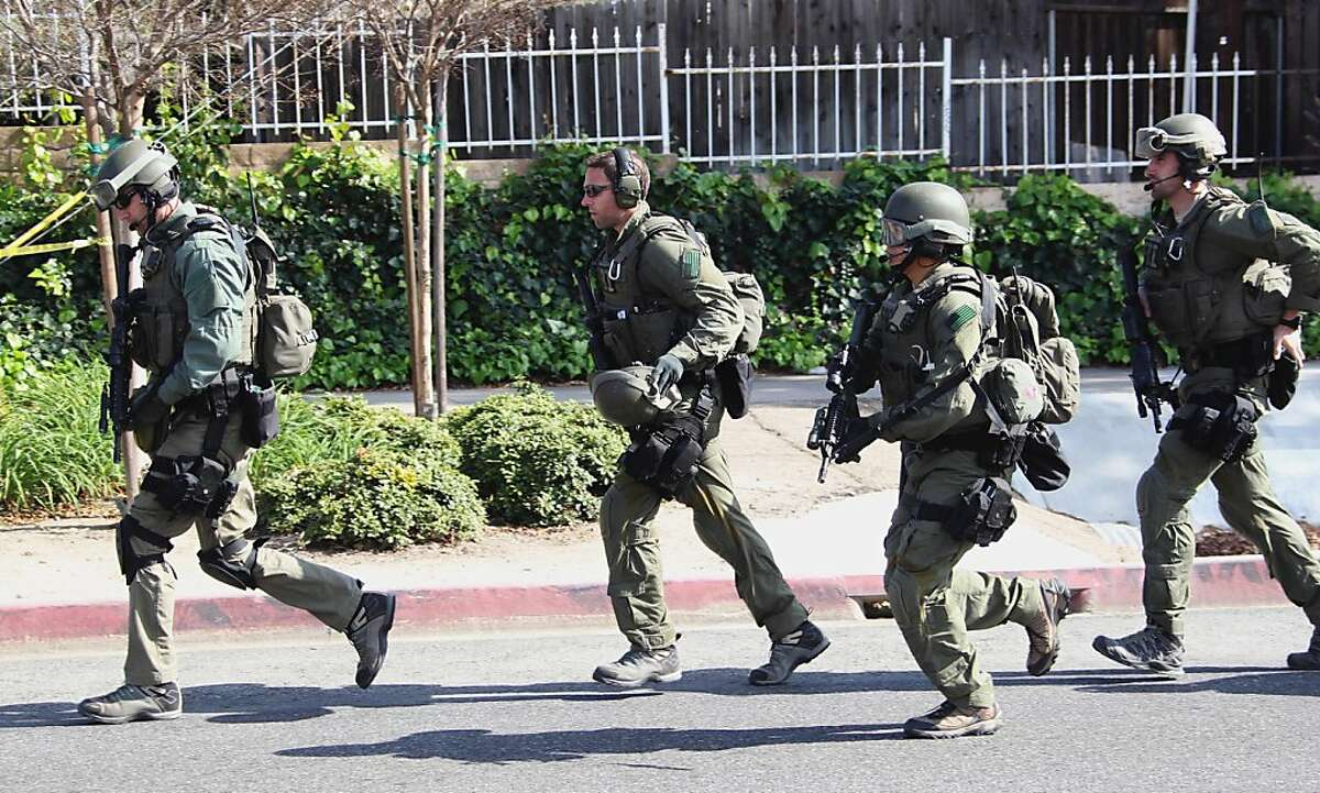 FBI SWAT members run near the perimeter of a bank standoff where a gunman is holding a bank manager hostage Thursday March 1, 2012, in Buena Park, Calif. A police spokesman says the demands of the hostage-taker are unknown. (AP Photo/Nick Ut)