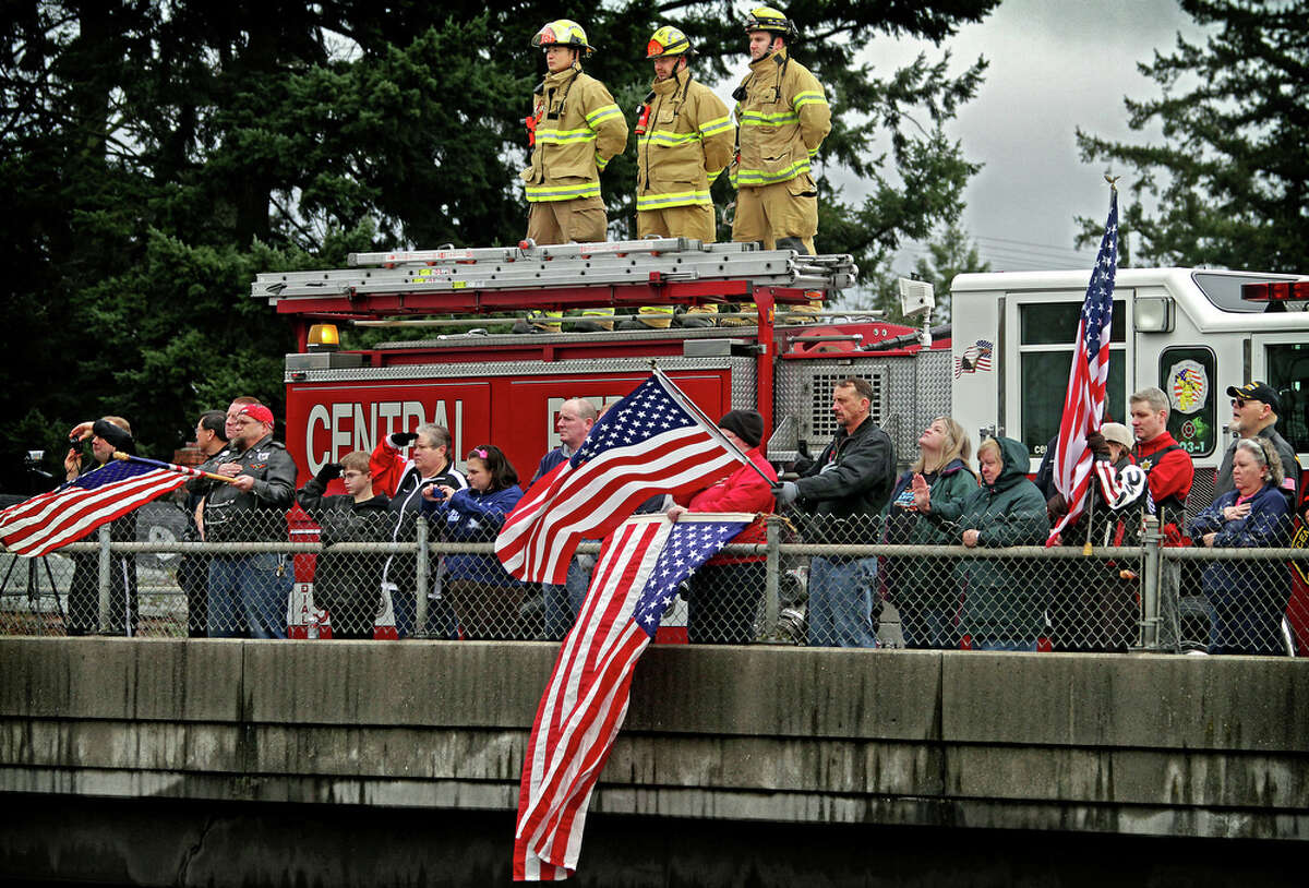 First responders from Central Pierce Fire & Rescue and the Pierce County Sheriff's Dept., join well wishers with flags and cameras on the Ainsworth overpass over Hwy. 512 in Parkland, Wash., on Thursday, March 1, 2012, to pay their respects during the procession for slain Washington State trooper Anthony Radulescu, 44, who was shot and killed Feb. 23 during a traffic stop in Ghorst. (AP Photo/The News Tribune, Dean J. Koepfler) TV OUT
