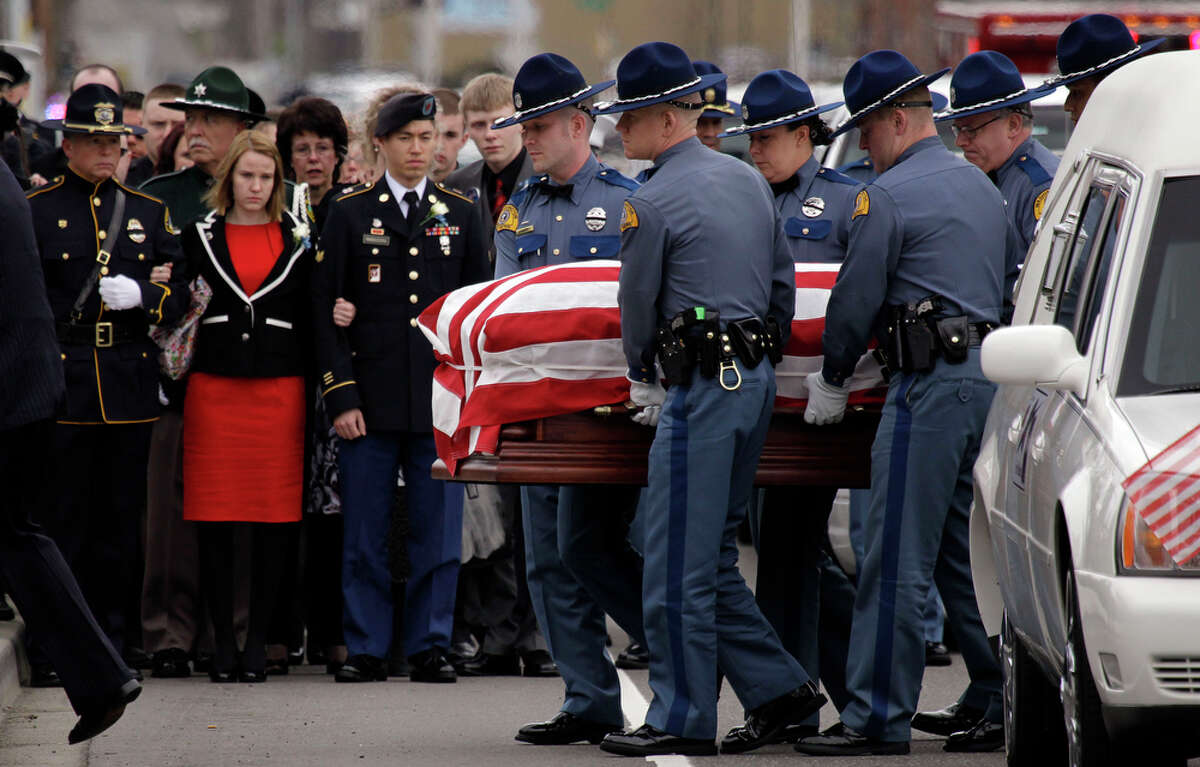 Family members look on as the body of Washington State Trooper Tony Radulescu is carried by fellow troopers to a memorial, Thursday, March 1, 2012, in Kent, Wash. Radulescu was shot and killed last week during a traffic stop in Gorst, Wash.