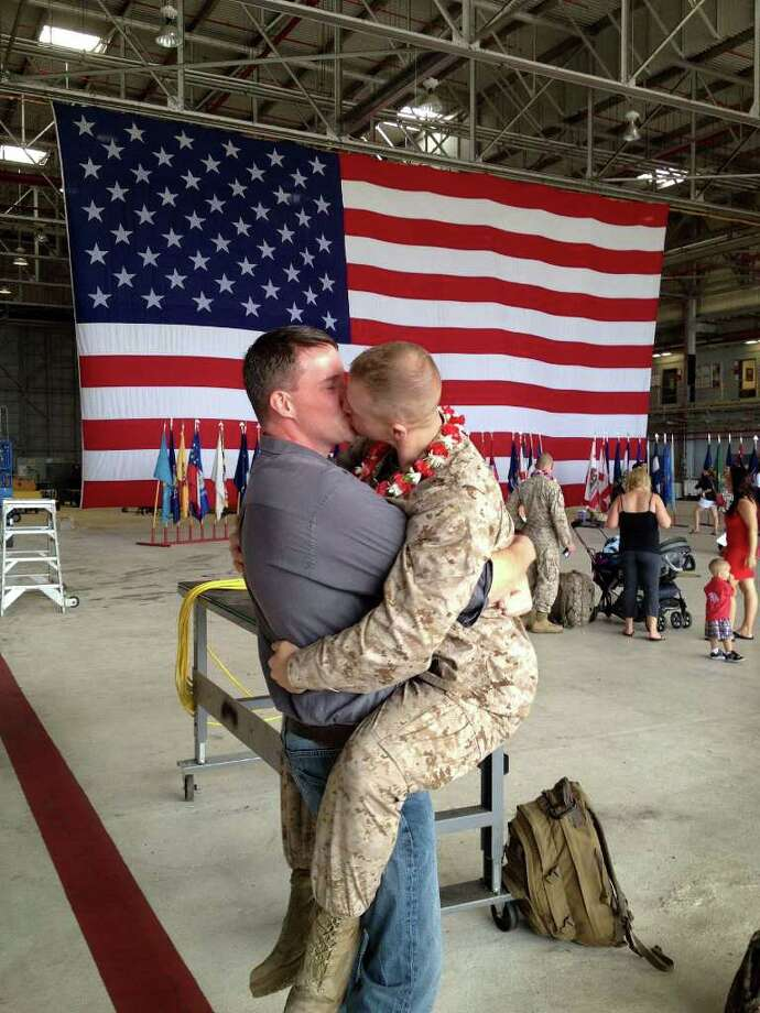 "Sgt. Brandon Morgan, right, is embraced by his partner Dalan Wells in a helicopter hangar at a Marine base in  Kaneohe Bay, Hawaii, upon returning from a six-month deployment to Afghanistan in this photo made Wednesday, Feb. 22, 2012.  The photo, made some five months after the repeal of the military's ""don't ask don't tell"" policy prohibiting gay servicemen from openly acknowledging their sexuality, is among the first showing a gay active duty serviceman in uniform kissing his partner at a homecoming. (AP Photo/David Lewis) Photo: David Lewis"