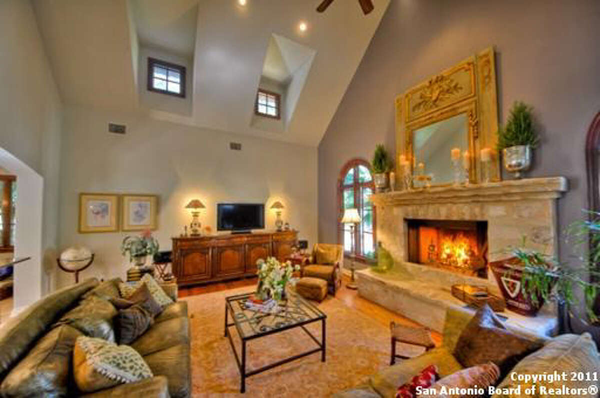 The den features a massive stone fireplace and a ceiling fan, with additional lighting of the small windows set near the high ceiling.