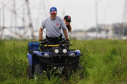 Volunteers with Texas Equusearch use ATVs to search along the Westpark Toll Rd. at Fondren for Kathy Lawson-Arrendondo, 37, who has been missing since Feb. 11. 