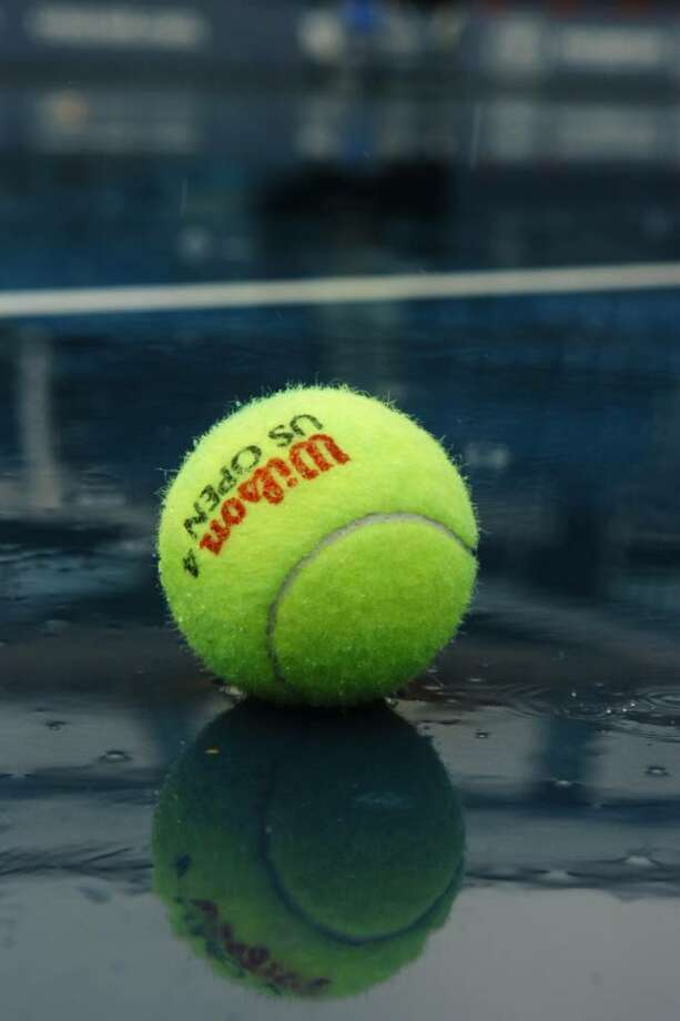 A soggy tennis ball sits in a puddle on the Stadium Court of the Connecticut Tennis Center, in New Haven, during Friday's rain. Photo: Ned Gerard / Connecticut Post