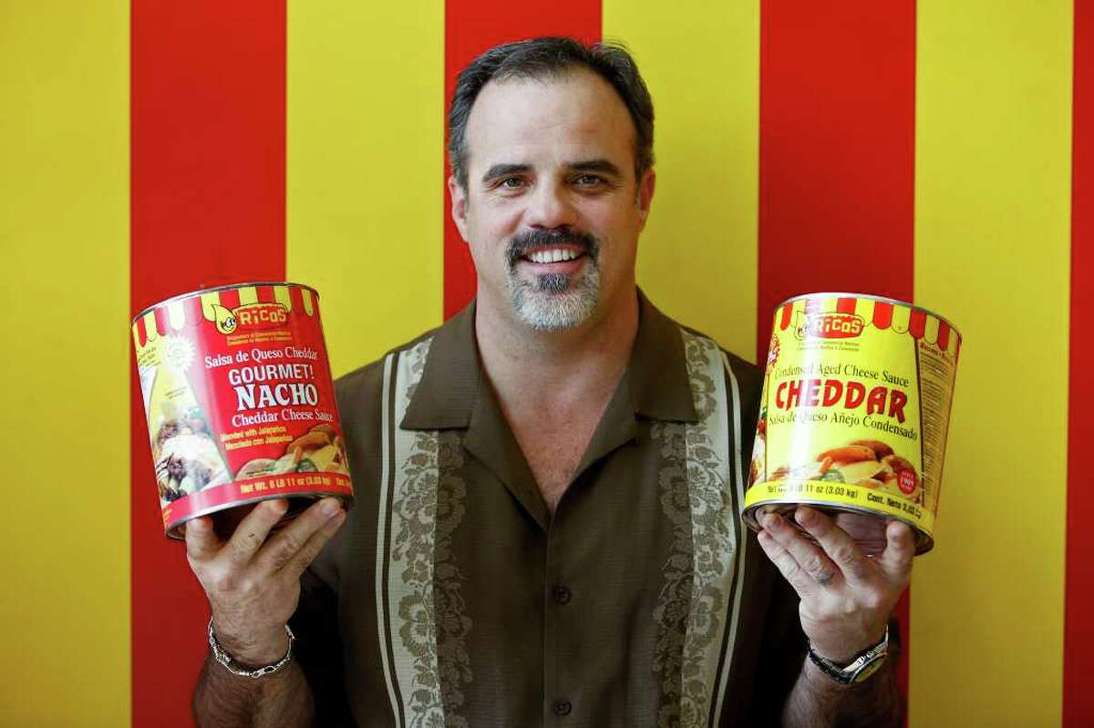 Tony Liberto, President of Ricos Products Company, holds cans of the cheese sauces the company is known for at the company's retail store at the offices in San Antonio on Wednesday, Feb. 29, 2012.