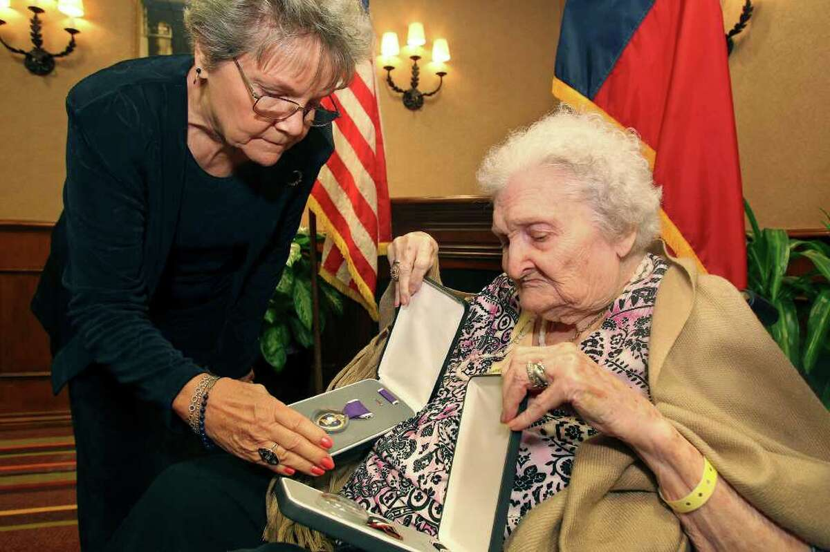 Elaine Wachtendorf checks the medals with her daughter Patsy Hill after she accepts the Purple Heart and Prisoner of War medals for her deceased father, Master Sgt. Charles Joyner, from Senator John Cornyn at the Omni Hotel at the Colonnade on March 2, 2012.