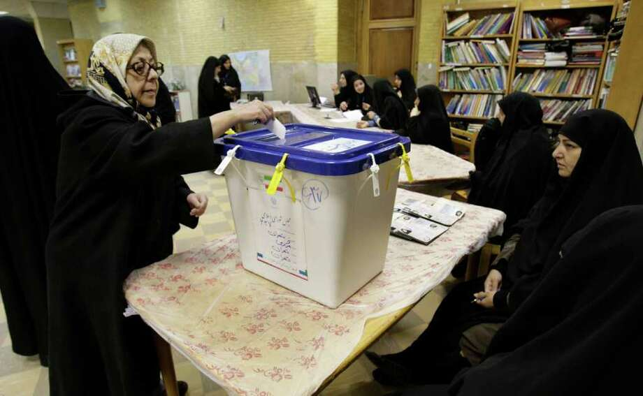 An Iranian woman casts her ballot for parliamentary elections at a polling station in Tehran, Iran, Friday, March 2, 2012. Nearly 47,000 polling stations throughout Iran take ballots for Iran's 290-member parliament, a vote seen as a political battleground for competing conservative factions in the absence of major reformist parties, which were kicked out of power over the 2009 post-election riots. More than 48 million Iranians are eligible to vote. Photo: AP