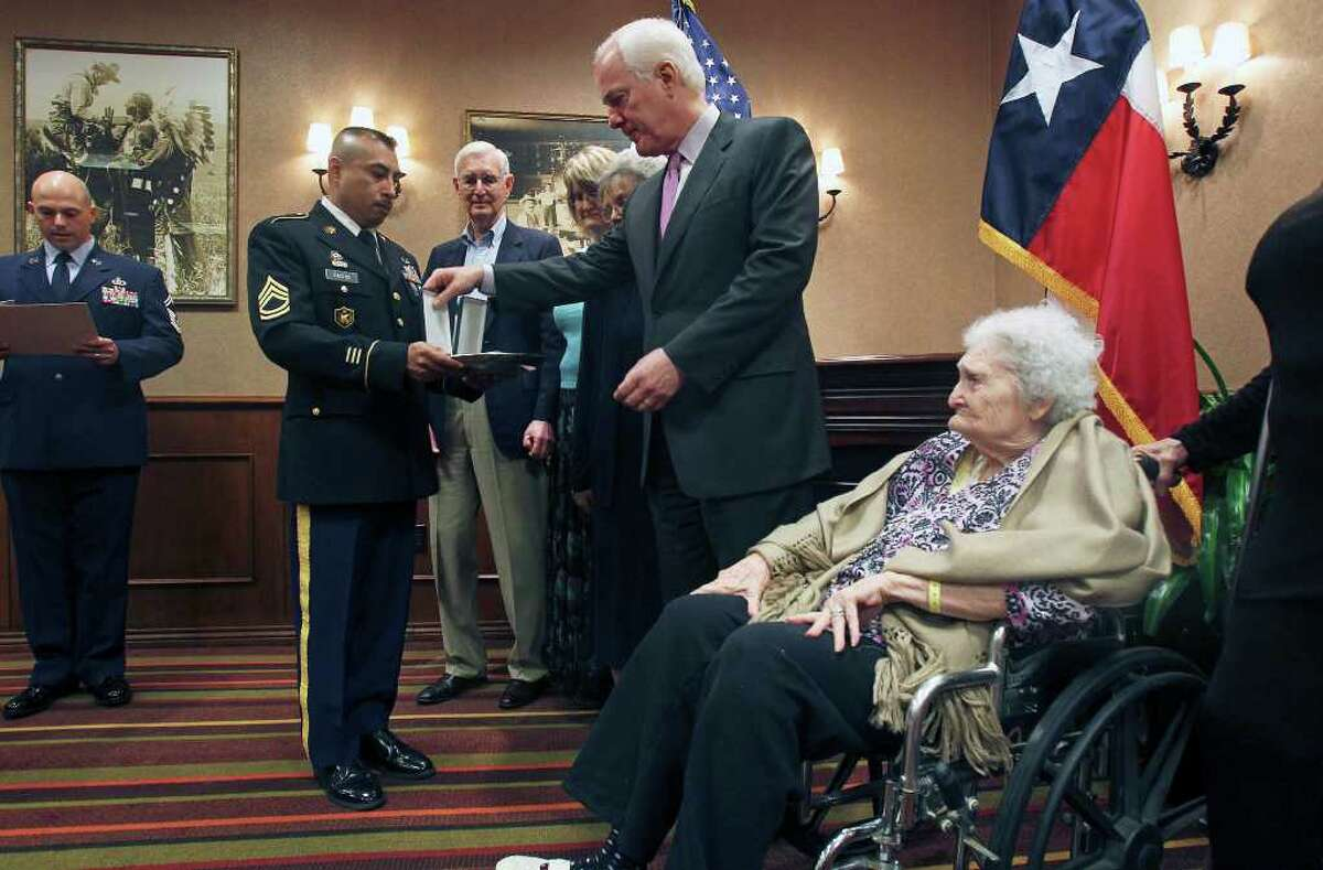Elaine Wachtendorf accepts the Purple Heart and Prisoner of War medals for her deceased father, Master Sgt. Charles Joyner, from Senator John Cornyn at the Omni Hotel at the Colonnade on March 2, 2012.