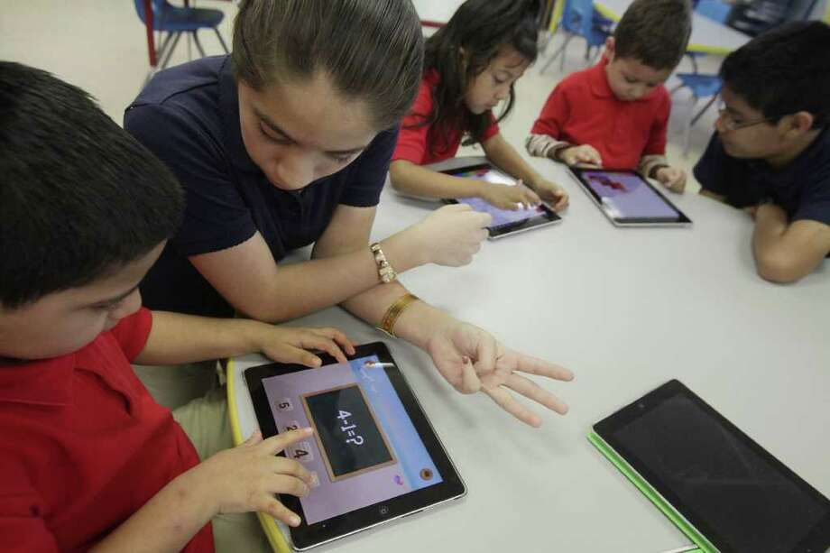 Julian Guevara Lopez, 5, gets help from student volunteer Esmeralda Vega, 12, during their iPad exercises at Rusk Elementary School on Thursday, Feb. 16, 2012, in Houston. Technology is changing the way students learn in the classroom at Rusk Elementary School, HISD science and technology magnet school, where approximately 70 iPads are available to be used for educational purposes. ( Mayra Beltran / Houston Chronicle ) Photo: Mayra Beltran / © 2012 Houston Chronicle