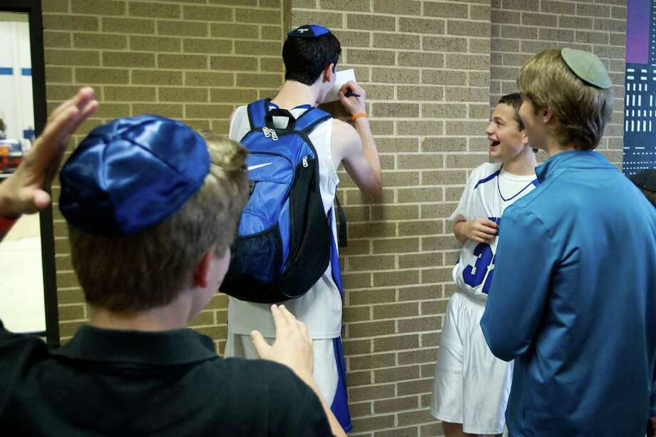 "Beren Academy guard Yoni Schiff (32) laughs as Beren Academy forward Zach Yoshor signs an autography for young fans after a TAPPS 2A state semifinal basketball game against Dallas Covenant at Nolan Catholic High School on Friday, March 2, 2012, in Fort Worth.  Of signing the autograph, Yoshor said, ""straight up, that was the coolest thing I've ever done.""  Beren originally forfeited the game because it interfered with observance of the Jewish Sabbath. After a lawsuit, the time and location of the game was changed. Beren won the game 58-46 to advance to the championship. Photo: Smiley N. Pool, Houston Chronicle / © 2012  Houston Chronicle"