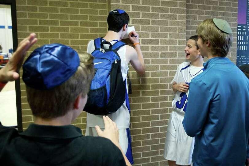Beren Academy guard Yoni Schiff (32) laughs as Beren Academy forward Zach Yoshor signs an autography