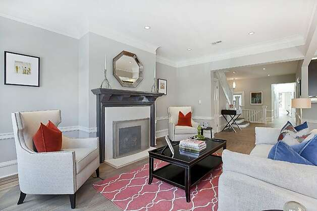 Deep crown molding and a fireplace create a warm feel in the living room. Photo: OpenHomesPhotography.com