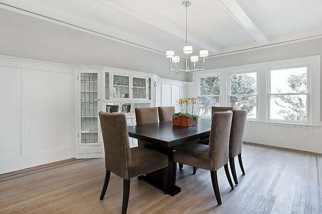 The dining room features built-in cabinetry and tall wainscoting. Photo: OpenHomesPhotography.com