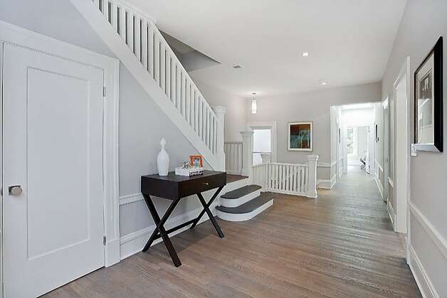 A wide hallway leads to a staircase that goes up and down. Photo: OpenHomesPhotography.com
