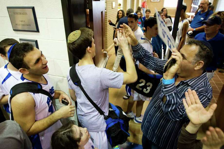 Beren Academy players celebrate with supporters following their victory over Dallas Covenant in a TAPPS 2A state semifinal basketball game at Nolan Catholic High School on Friday, March 2, 2012, in Fort Worth.  Beren originally forfeited the game because it interfered with observance of the Jewish Sabbath. After a lawsuit, the time and location of the game was changed. Beren won the game 58-46 to advance to the championship. Photo: Smiley N. Pool, Houston Chronicle / © 2012  Houston Chronicle