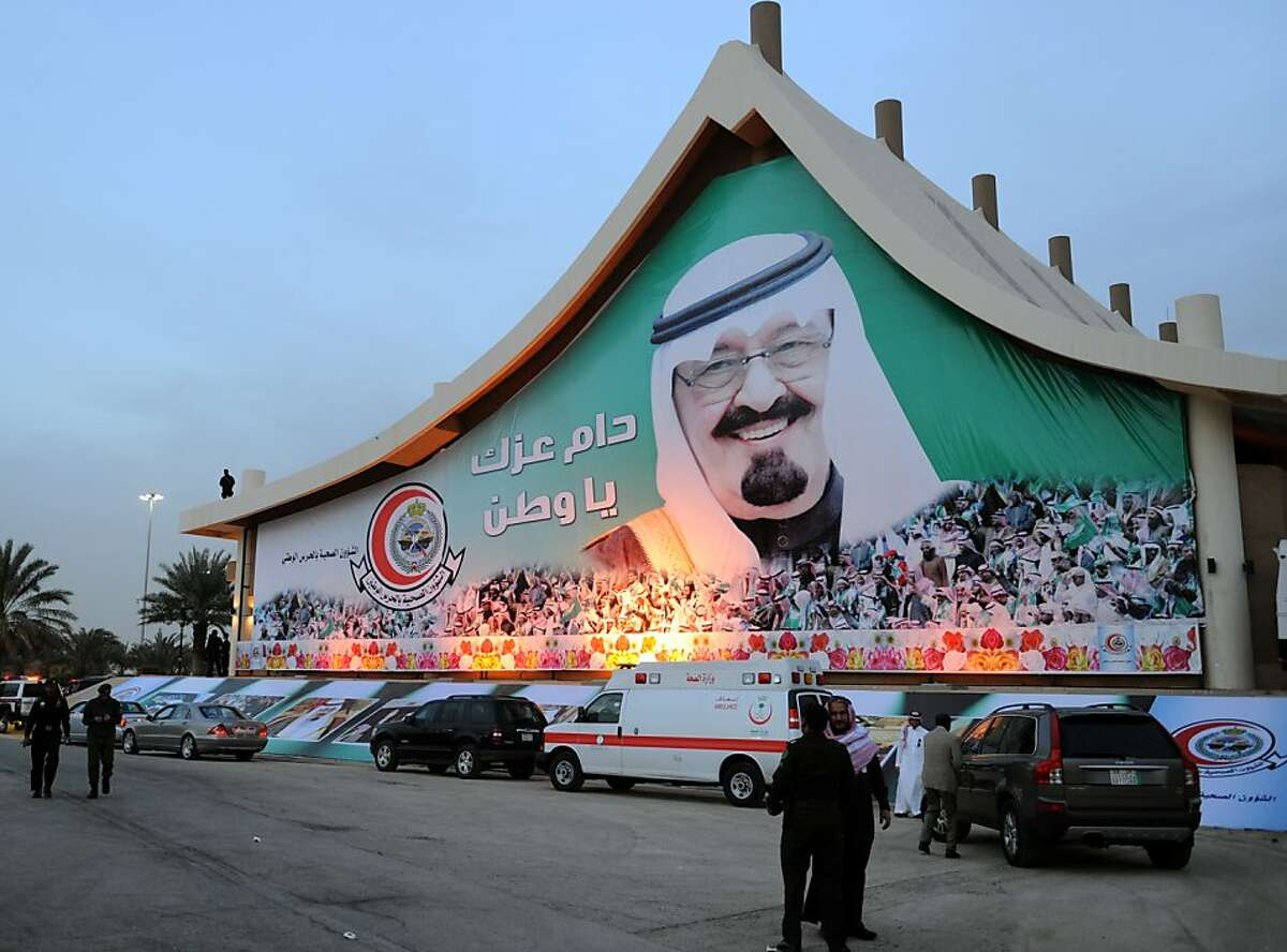 Saudi security personnel stand in front of a huge poster of King Abdullah bin Abdulaziz during the annual Janadriyah Festival of Heritage and Culture on the outskirts of the capital Riyadh on February 8, 2012. AFP PHOTO/FAYEZ NURELDINE (Photo credit should read FAYEZ NURELDINE/AFP/Getty Images)