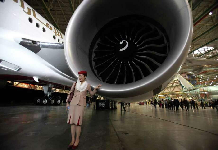 Emirates flight attendant Naoko Fukuda poses next to the engine of Boeing's 1,000th 777 during a ceremony marking the completion of the 1,000th 777 at the assembly plant in Everett on Friday, March 2, 2012. Photo: JOSHUA TRUJILLO / SEATTLEPI.COM