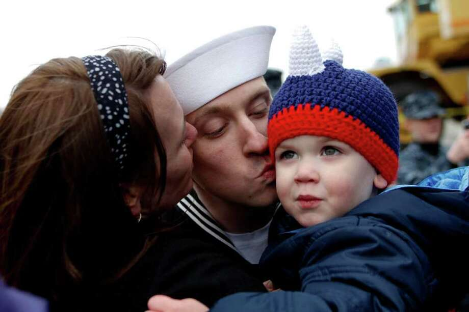 Amy Shears gives her husband Justin Shears a kiss as he kisses their son will after returning from a seven month deployment aboard the USS John C. Stennis aircraft carrier on Friday, March 2, 2012. Photo: JOE DYER / SEATTLEPI.COM