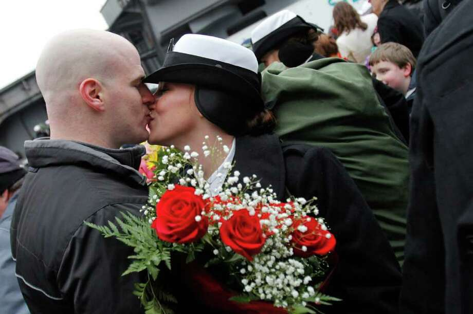 Nathan Foster kisses his girlfriend Emily Walter after she returns from her seven month deployment aboard the USS John C. Stennis, at Naval Base Kitsap, Bremerton WA. Friday, March 2, 2012. Photo: JOE DYER / SEATTLEPI.COM