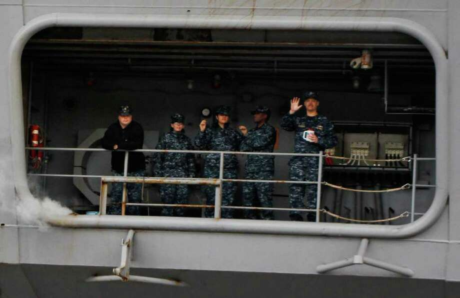 Sailors wave to their loved ones as they return to Naval Base Kitsap in Bremerton WA. on Friday, March 2, 2012. They had been deployed on the USS John C. Stennis for the last seven months. Photo: JOE DYER / SEATTLEPI.COM