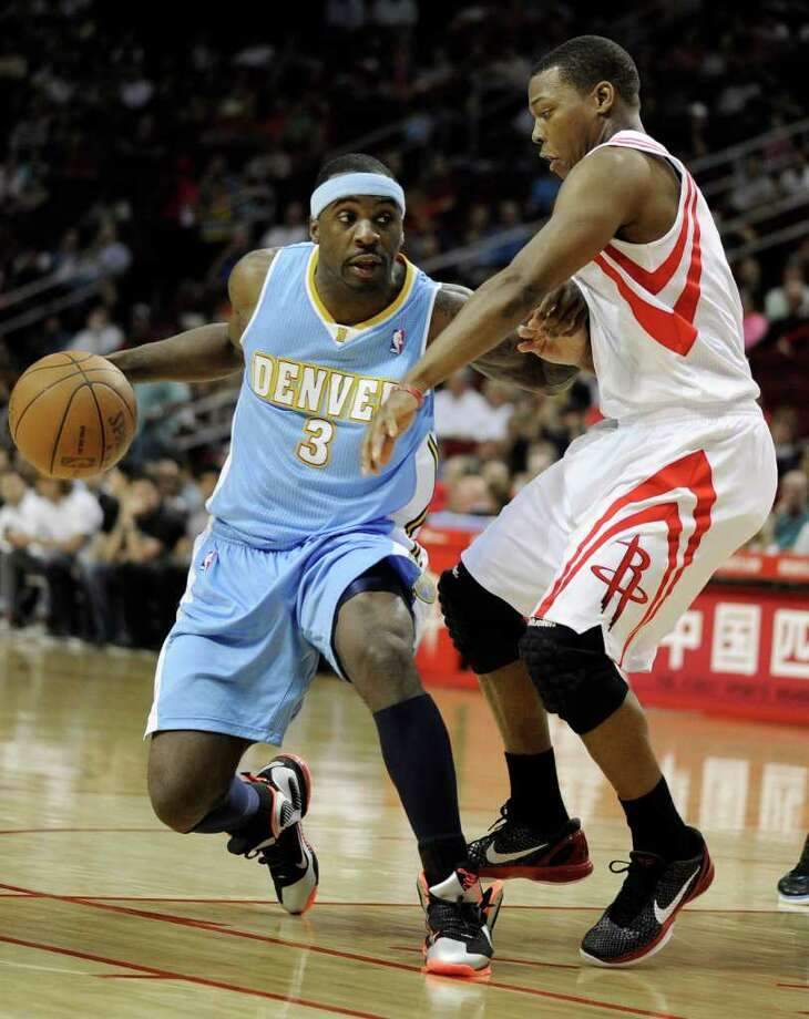 Denver Nuggets' Ty Lawson (3) pushes off Houston Rockets' Kyle Lowry, right, in the first half of an NBA basketball game Friday, March 2, 2012, in Houston. (AP Photo/Pat Sullivan) Photo: Pat Sullivan, Associated Press / AP