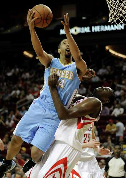 Denver Nuggets' Andre Miller, left, goes up against Houston Rockets' Samuel Dalembert, right, for a
