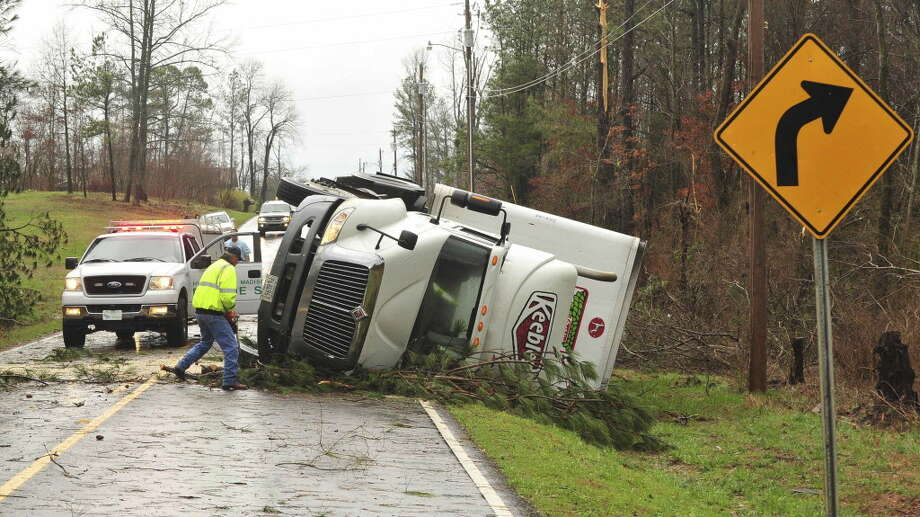 A 18-wheeler is  flipped on it's side on Friday morning March 2, 2012 in Harvest, Ala. A reported tornado destroyed several houses in northern Alabama as storms threatened more twisters across the region Friday. Photo: Eric Schultz, Associated Press / The Huntsville Times