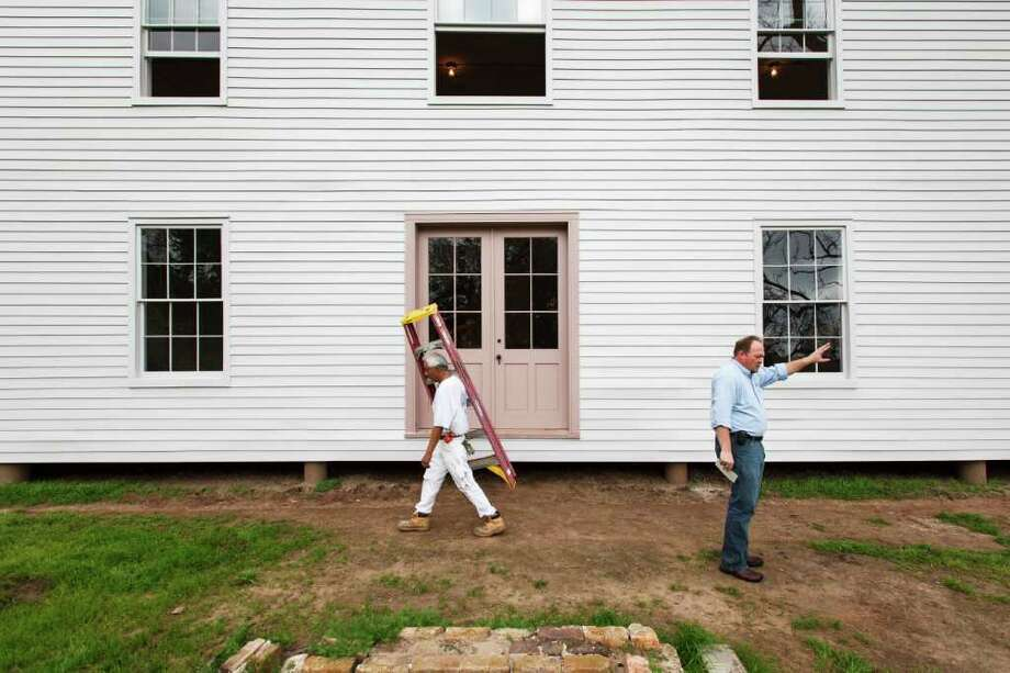 Bryan McAuley, Site Manager, points to a window as Marcos Bailon walks by the two-story Greek Revival-style plantation house at the Levi Jordan Plantation State Historic Site in Brazoria. The site consists of the plantation house, currently undergoing exterior restoration, and significant archeological remains, including the slave quarters. Photo: Michael Paulsen, Houston Chronicle / © 2012 Houston Chronicle
