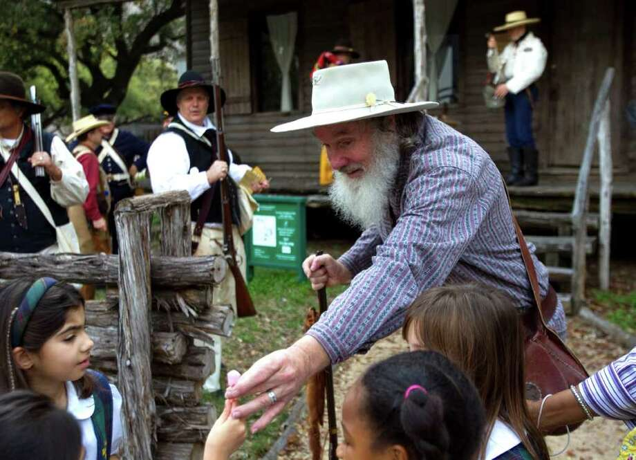John Lightfoot, of the Texas Army, hands out paper flowers to schoolchildren outside the 1823 Old Place cabin at Sam Houston Park Friday, March 2, 2012, in Houston. The Texas Army commemorated Texas Independence Day Friday. The Texas Army is dedicated to the purposes of perpetuating the memory of those early Texas patriots who worked and fought as the first army of the Republic of Texas. Photo: Brett Coomer, Houston Chronicle / © 2012 Houston Chronicle