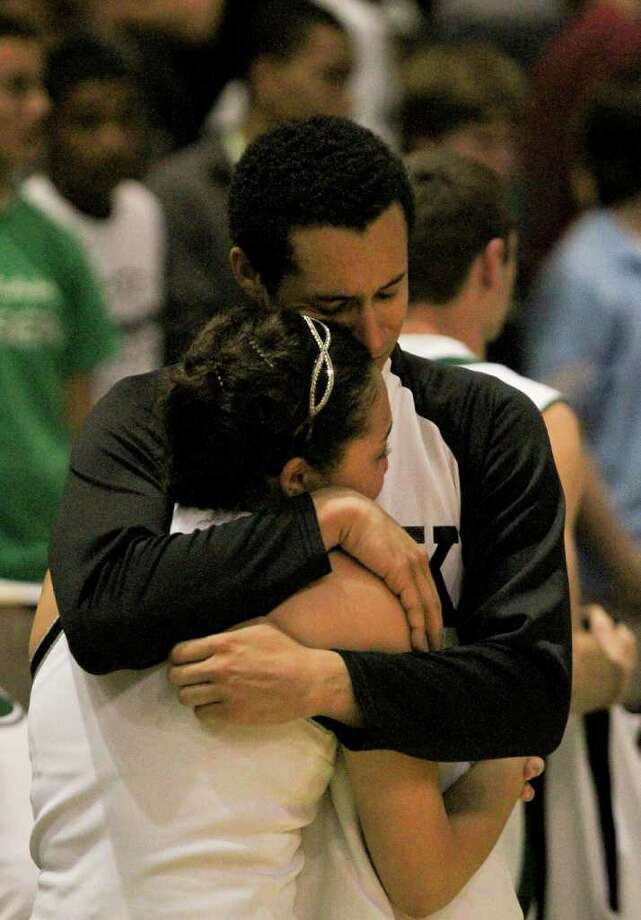 3/2/2012: Andre Davidson #20 is comforted by a cheerleader after Kingwood Park lost to Yates  in the 4A regional semifinals high school mens basketball game at the Merrell Center in Katy, Texas. Yates won 69 to 61. Photo: Thomas B. Shea, For The Chronicle / © 2012 Thomas B. Shea