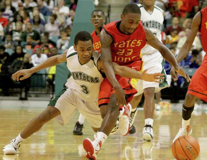 3/2/2012: Darrion martin #23 of Yates and Jaylon Henderson #3 of Kingwood Park fight over a loose ba