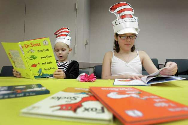 Julia Cobb, 6, left, of Birmingham, AL and Thalia Villalva, 8, of El Paso,  both patients at MD Anderson Children's Cancer Hospital, read Dr. Seuss books during a celebration of Dr. Seuss's birthday, Friday, March 2, 2012, in Houston. Photo: Melissa Phillip, Houston Chronicle / © 2012 Houston Chronicle
