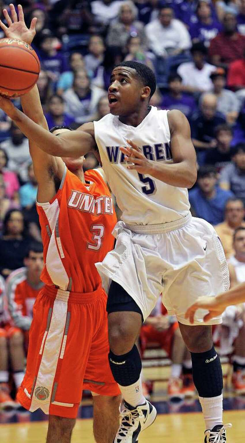 Marcus Keene turns for a quick shot in the lane for the Warriors against Raul Moreno as Warren beats Laredo United 83-50 in the first round of the Region IV 5A basketball tournament at the UTSA Convocation Center on March 2, 2012 Tom Reel/ San Antonio Express-News