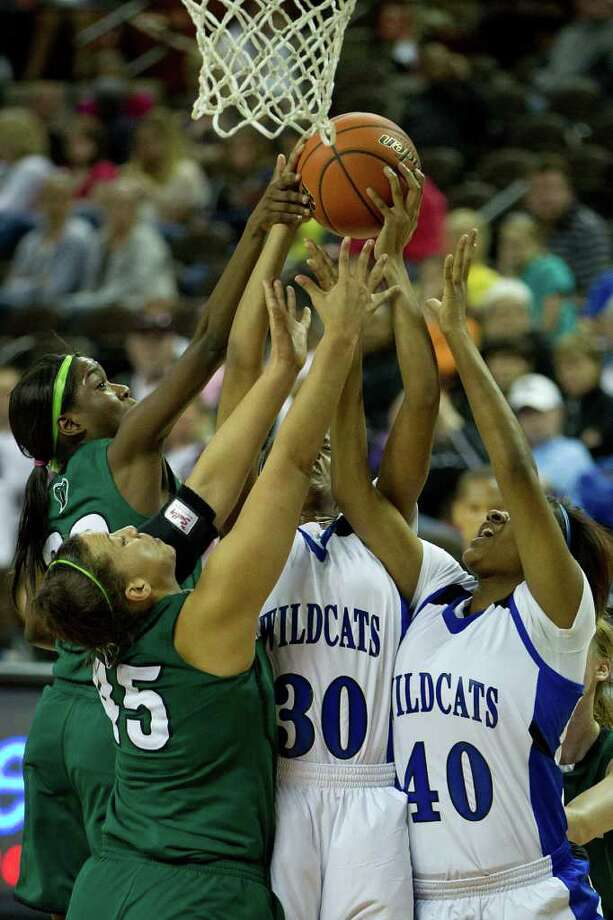 Spring Dekaney forward Shunta Nevitt (30) and forward/center Kadetra O'Brine (40) fight for a rebound against San Antonio Reagan guard Moriah Mack (32) and center Corrigan Tibbs (45) during first half action in a class 5A semifinal game during the UIL girls state basketball tournament at the Frank Erwin Center on Friday, March 2, 2012, in Austin. Mansfield Summit won the game. Photo: Smiley N. Pool, Houston Chronicle / © 2012  Houston Chronicle