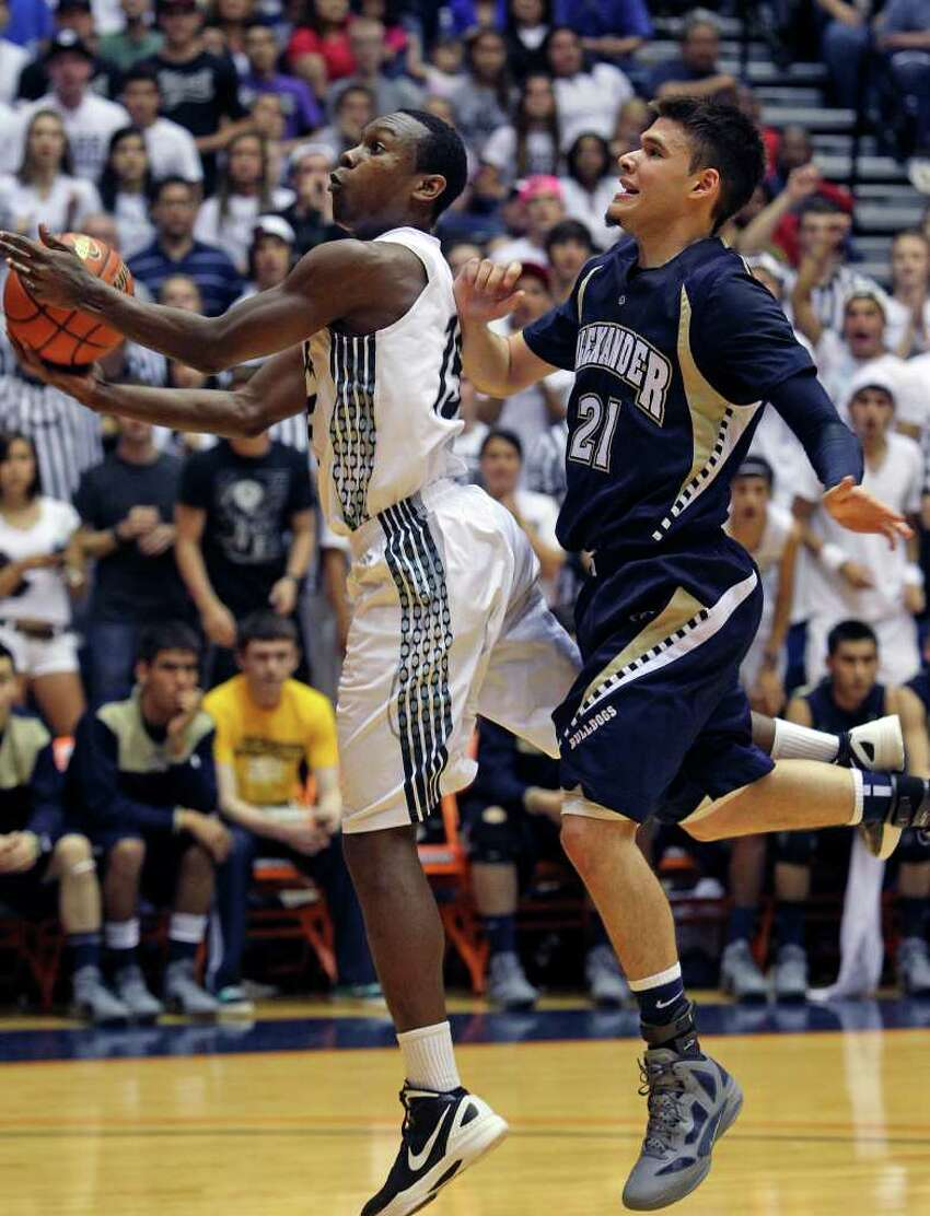 Cougar guard Carter Josephs floats to the hoop in front of Diego Solis as Clark beats Laredo Alexander 58-51 in the first round of the Region IV 5A basketball tournament at the UTSA Convocation Center on March 2, 2012 Tom Reel/ San Antonio Express-News