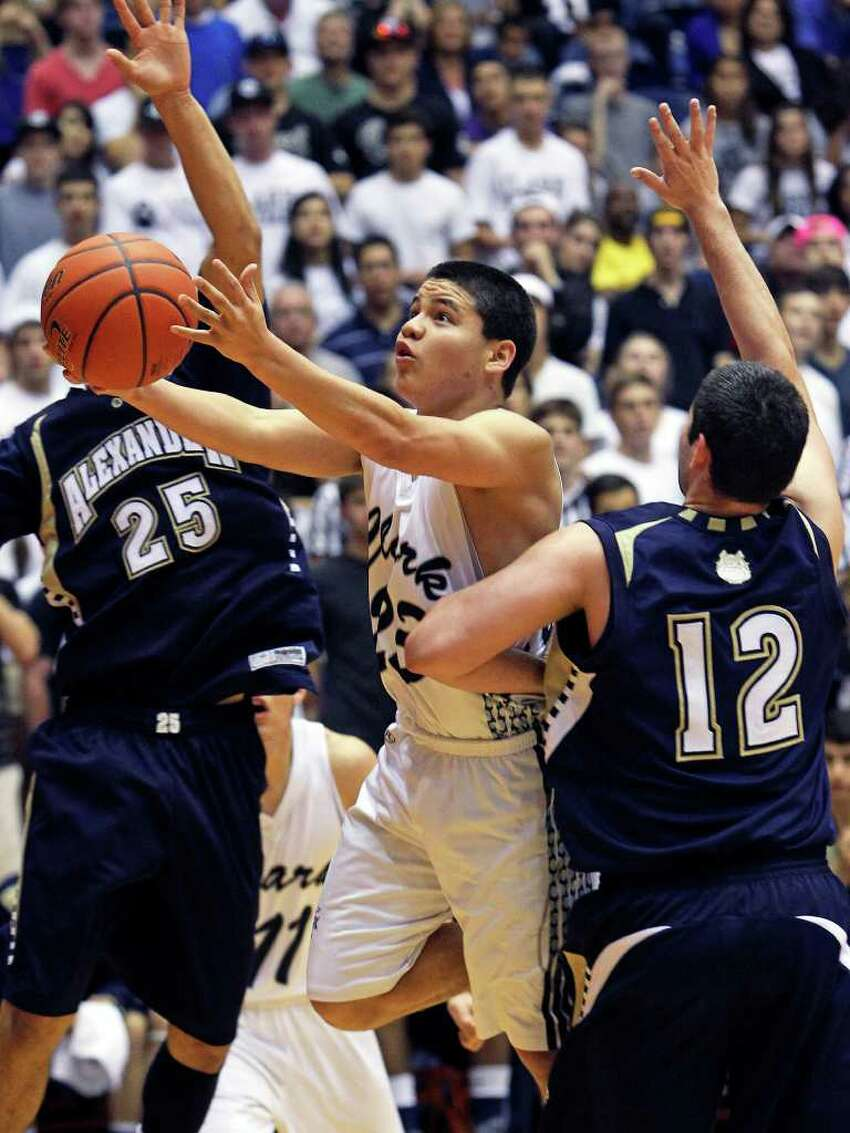 Cougar guard Justin Brickman finds a way through defenders Brian Swain (25) and Philip Connor for a layup as Clark beats Laredo Alexander 58-51 in the first round of the Region IV 5A basketball tournament at the UTSA Convocation Center on March 2, 2012 Tom Reel/ San Antonio Express-News